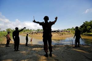 Members of BGB command to the Rohingya people not to cross the canal, who take shelter in No Man's Land between Bangladesh-Myanmar border, in Cox's Bazar